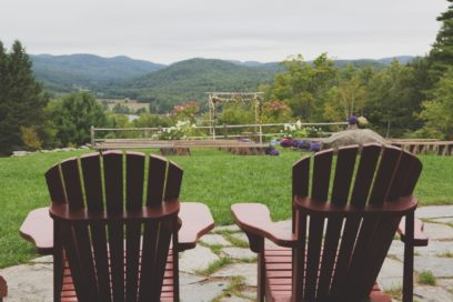 Two lawn chairs with a view of an outdoor wedding set up.