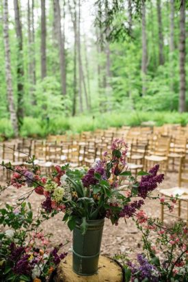 A vase of flowers at an outdoor wedding venue.