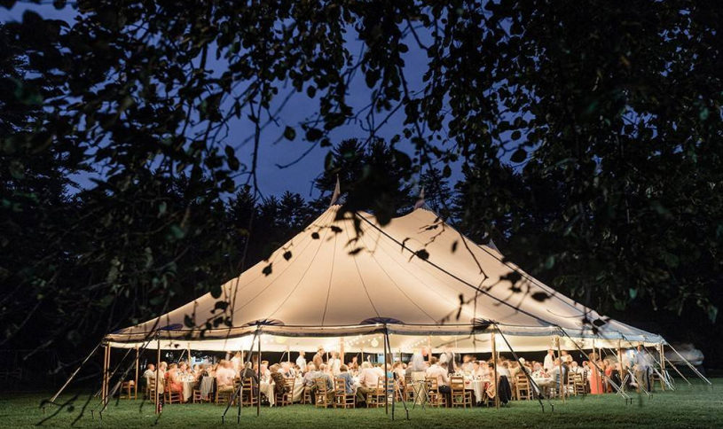 A large white tent over guests sitting at tables.