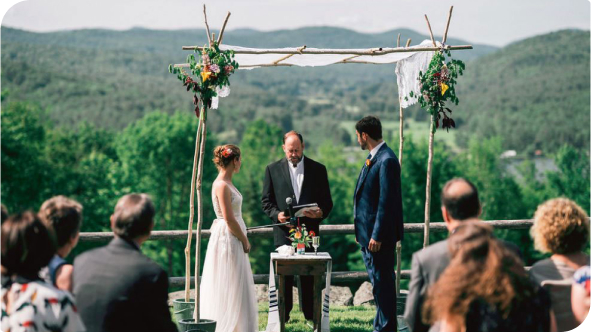 A couple at the altar at an outdoor wedding.