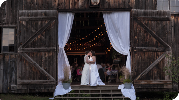 A married couple sharing a kiss at the entrance of a barn.