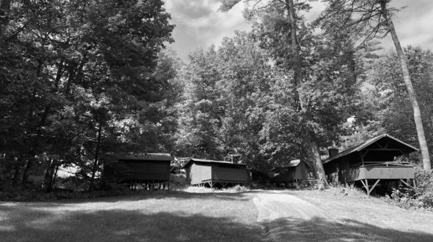 A black and white view of open air cabins surrounded by trees.