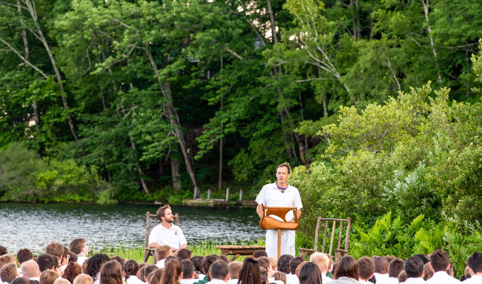 A staff member speaking at an assembly.