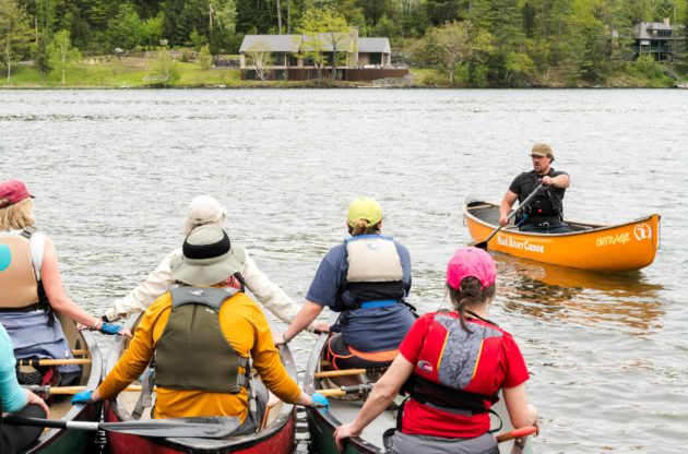 Groups of people on canoes as an instructor demonstrates.