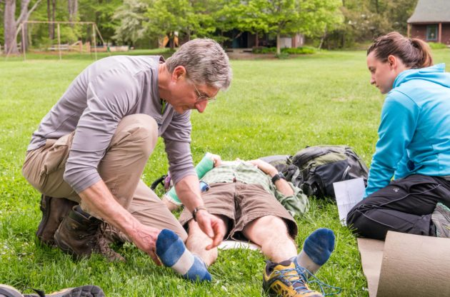 A man examine's another person's leg.