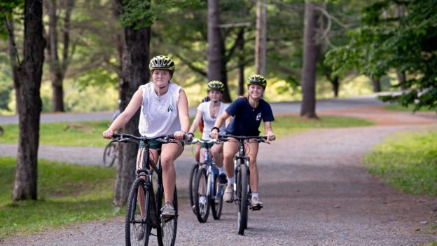 A group of campers biking on a trail.