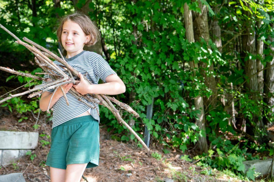 A Hive camper holding a bunch of sticks.