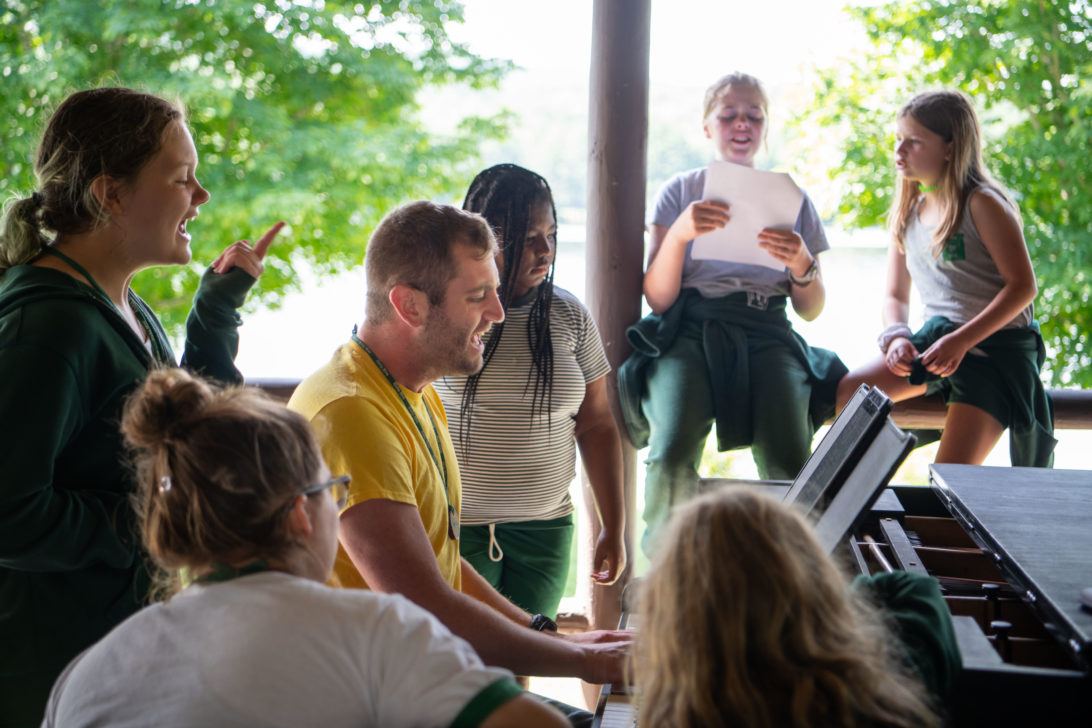 Campers singing around the piano.