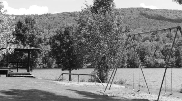 A black and white view of a swing set.