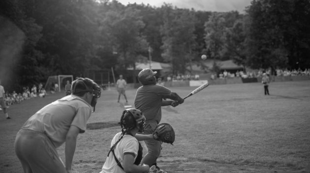 A black and white view of people playing baseball.