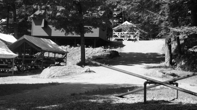 A black and white view of a seesaw and an open air cabin.