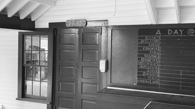 A black and white view of a door and a chalkboard.