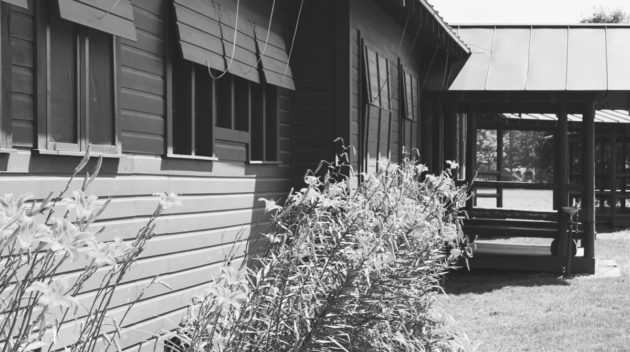 A black and white view of the outside of a lodge.