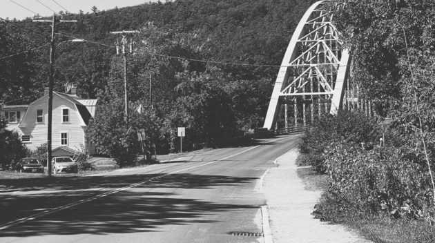 A black and white view of a road leading to a bridge.