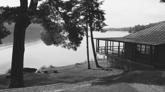 A black and white view of a lodge overlooking a lake.
