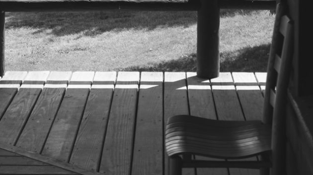 A black and white view of a chair on a porch.