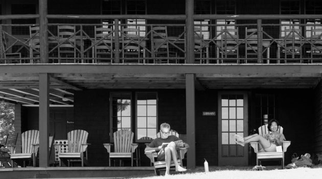 A black and white view of two campers relaxing on lawn chairs.