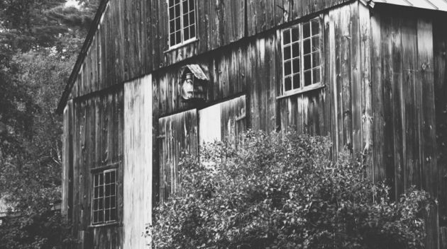 A black and white view of a barn.