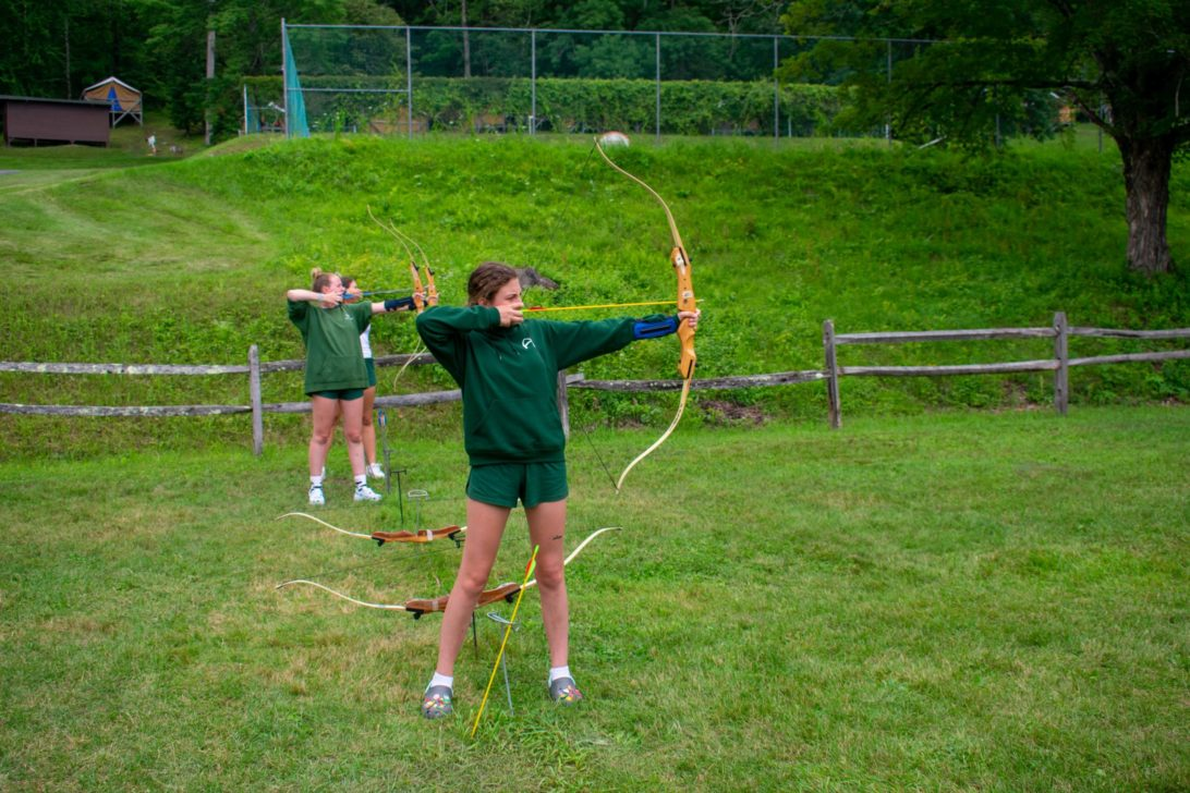 Campers shooting a bow and arrow.