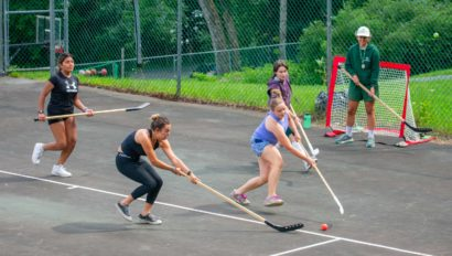 Campers playing street hockey.