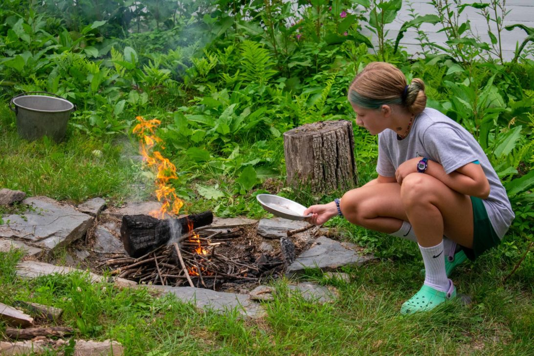 A camper cooking over a campfire.