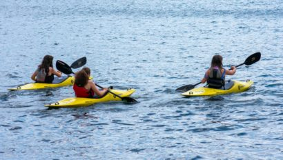 Three campers kayaking on a lake.