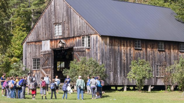 A group of campers standing outside of a barn.