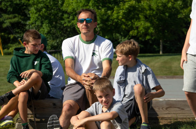 A camp staff member sitting with campers.
