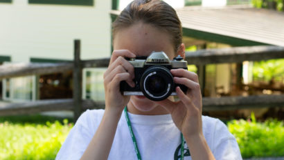 A camper looking through a film camera.