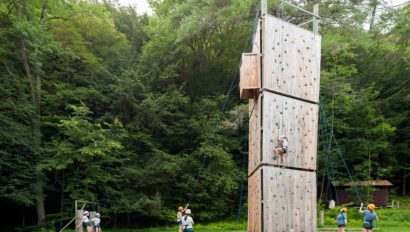 Campers climbing a rock climbing wall outside.