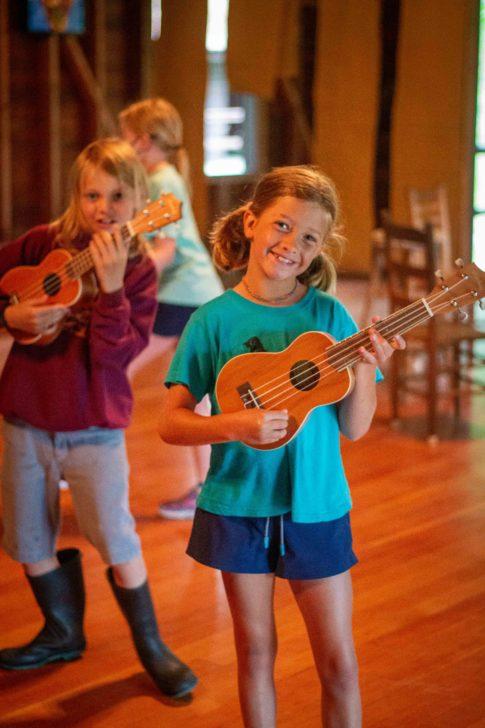 A girl playing a ukulele.