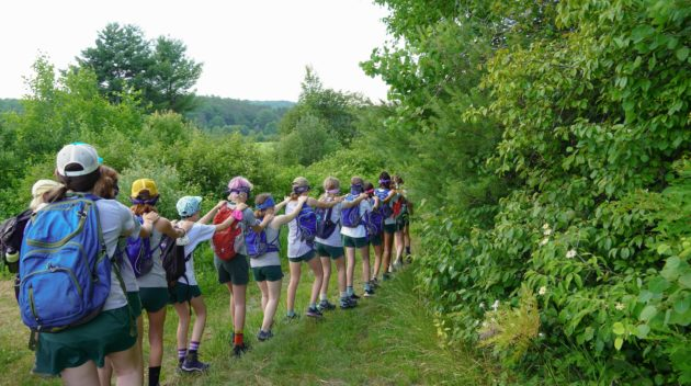 A group of campers walking in a line with their hands on each other's shoulders.