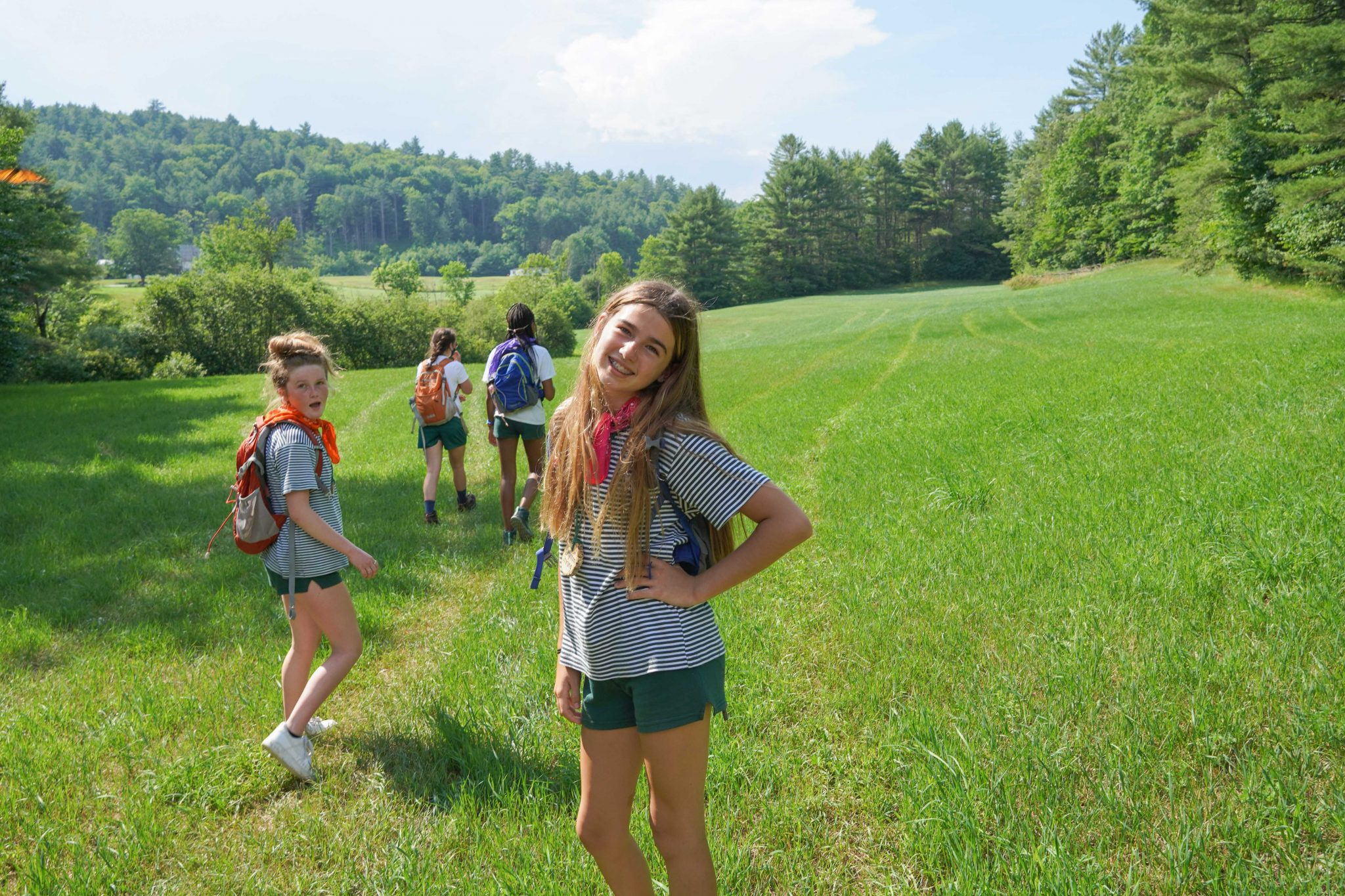 A smiling Hiver with a small camper group in a grassy field on a hike.