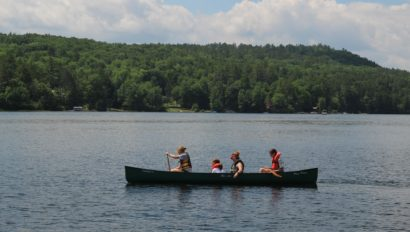 A group of four campers canoeing together.