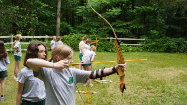 A camper learning how to shoot a bow and arrow.