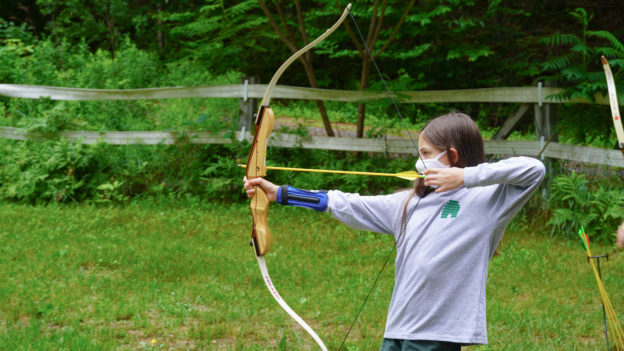 A camper learning how to shoot an arrow.