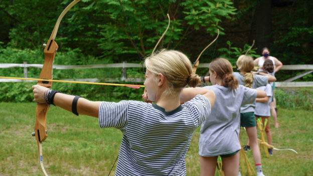 Campers aiming bow and arrows.