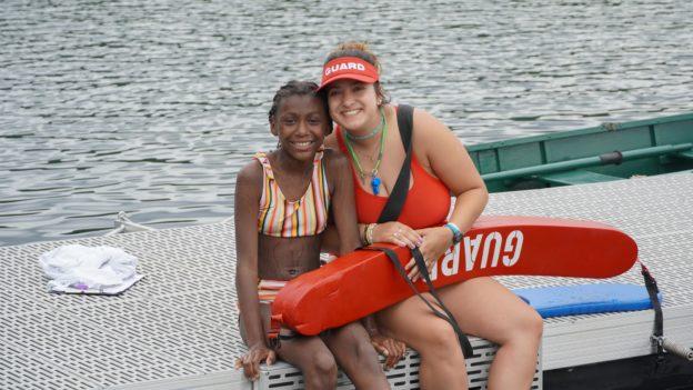 A lifeguard and a camper smiling.