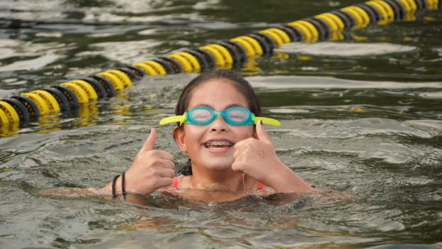 A camper swimming and giving the thumbs up sign.