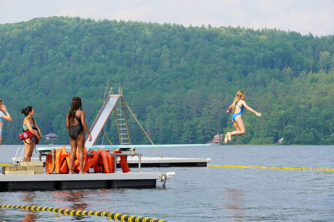 Campers diving off the dock.