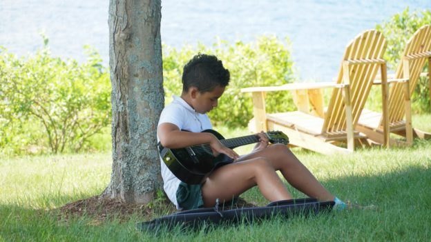 A camper sitting under a tree playing the guitar.