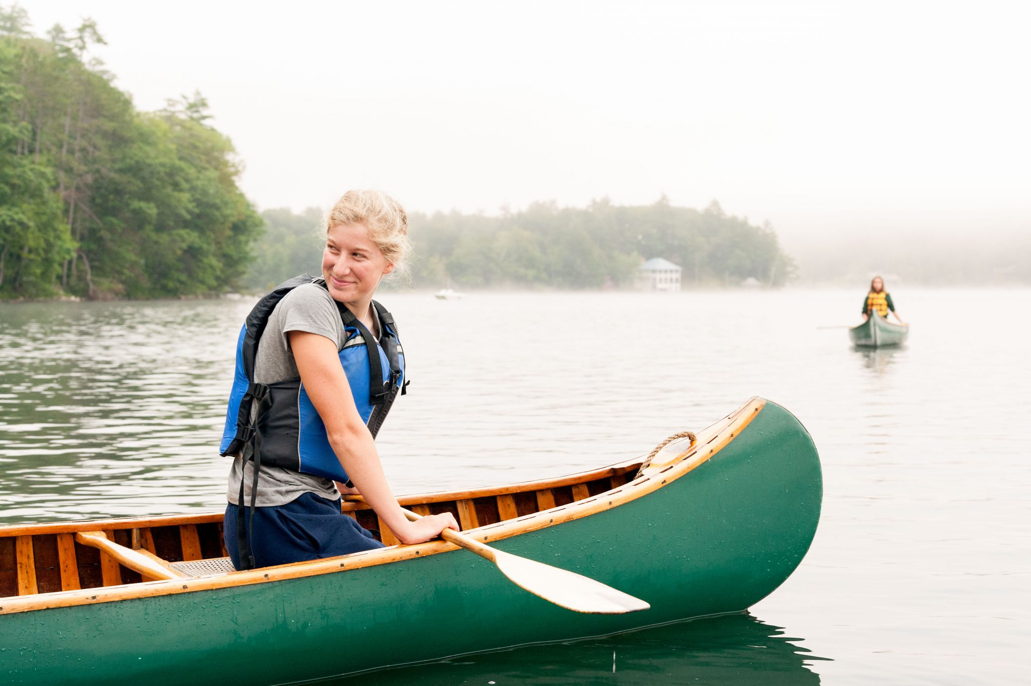 An Aloha camper smiling in a canoe on the lake.