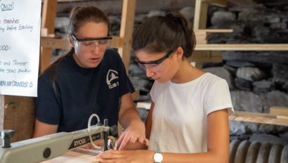 A camper working in the woodshop with an counselor's guidance.