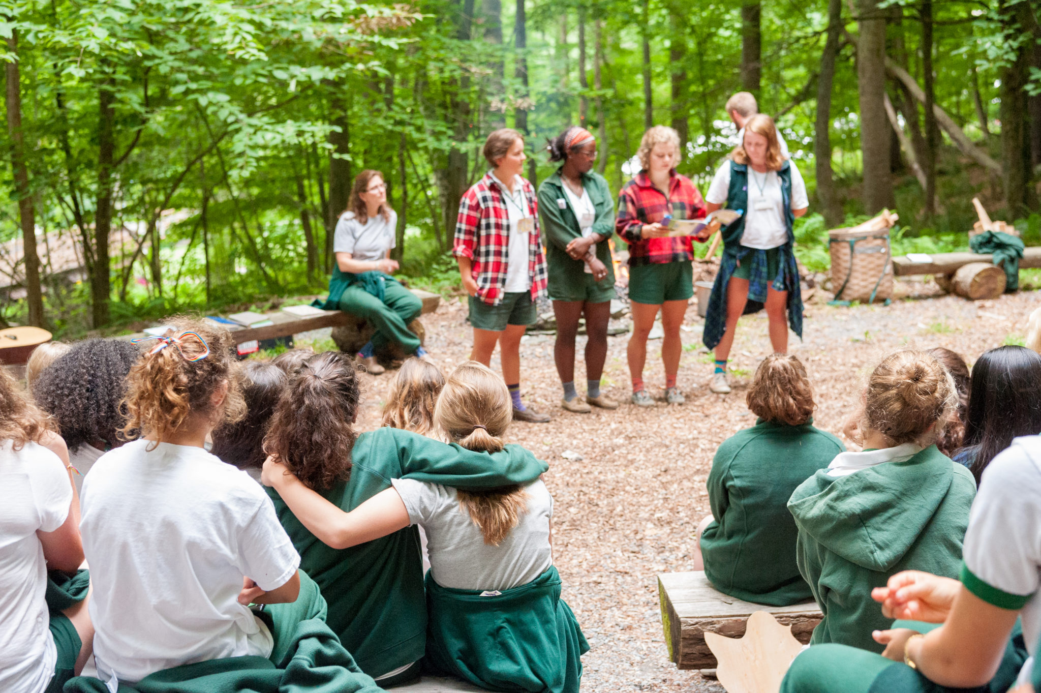 A group of counselor reading to the camp at a special spot in the Aloha woods called wedding ring.