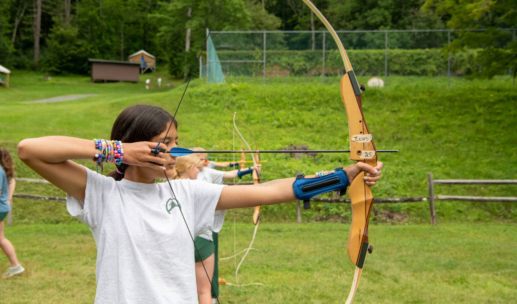 Camper drawing back a bow to shot an arrow at archery.