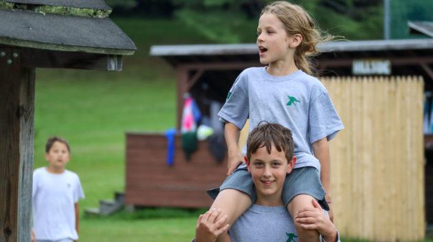 A camper sitting on another camper's shoulders.