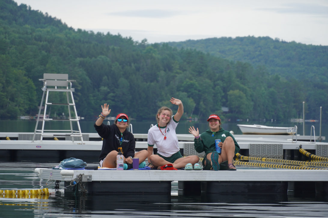 Three people waving from a dock on the water.