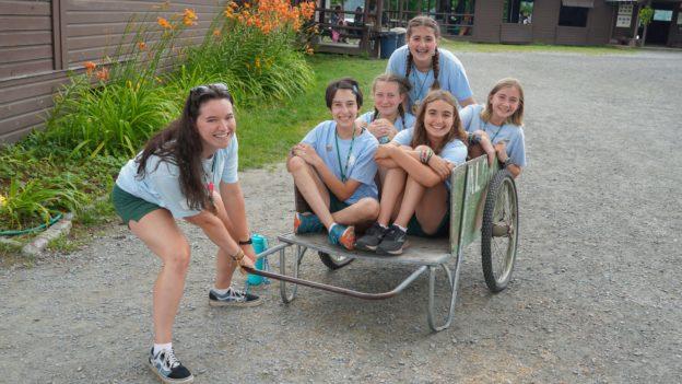 Campers sitting in a wheelbarrow.