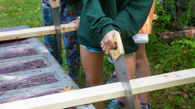 A camper cutting a piece of wood with a handsaw.