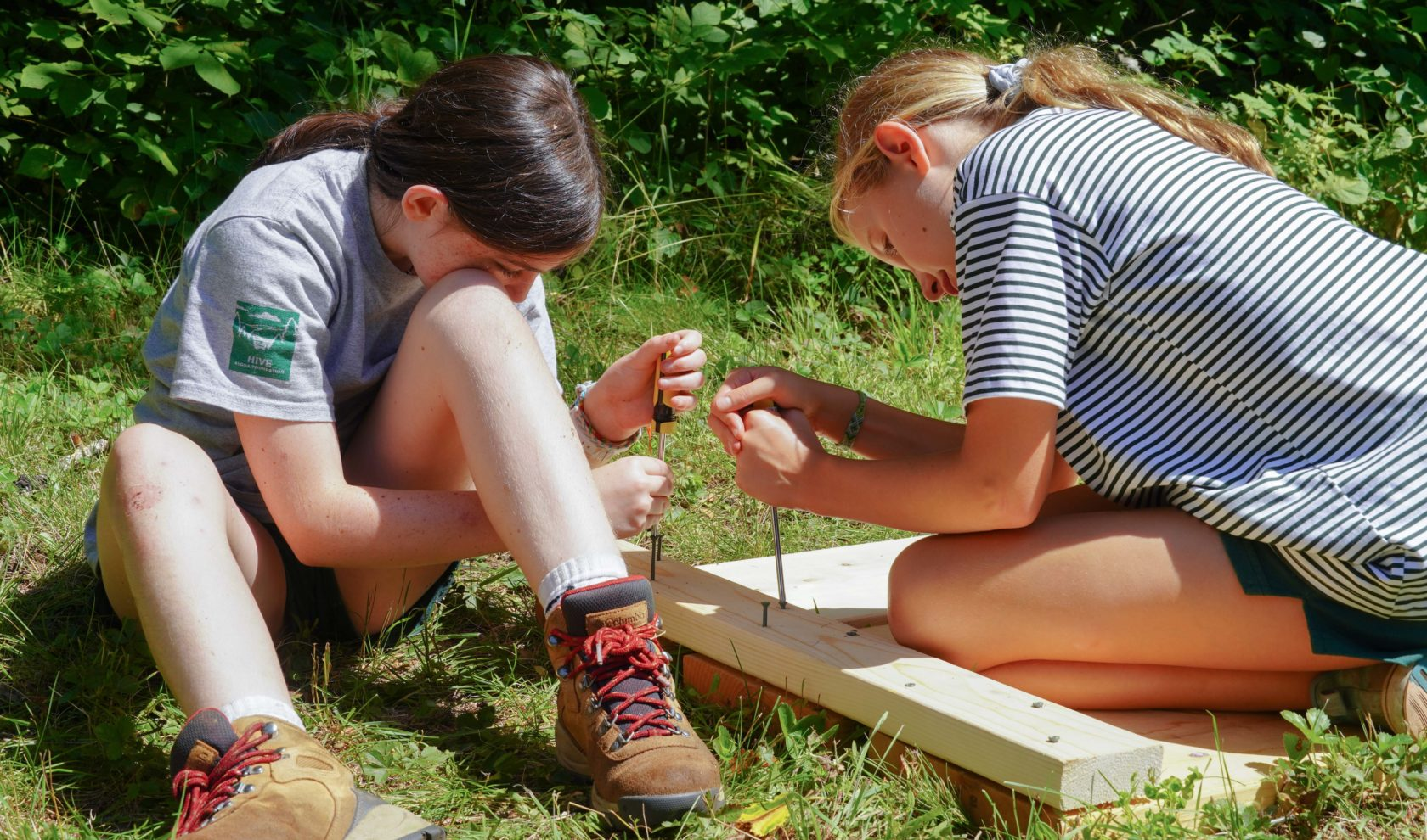 Two girls working with wood and nails.